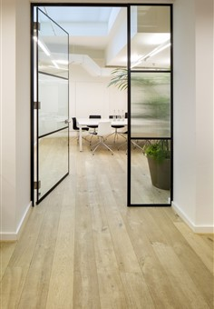 Hallway with glass doors contains Hakwood Muse flooring