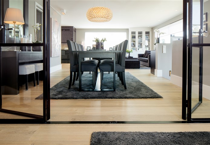 Look through glass doors with view at living room with Hakwood Locke flooring