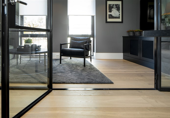 Look through glass doors with view at seating area with Hakwood Locke flooring